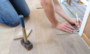 A man installing wood floor tiles